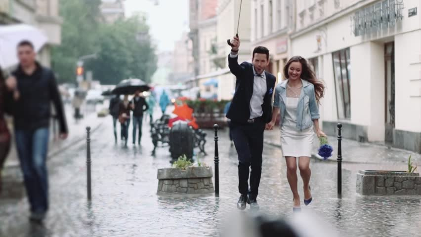 Young handsome bearded man in an elegant costume and tiny attractive woman in casual wear with cornflower bouquet. Young people running under the umbrella in the city center under the heavy rain.