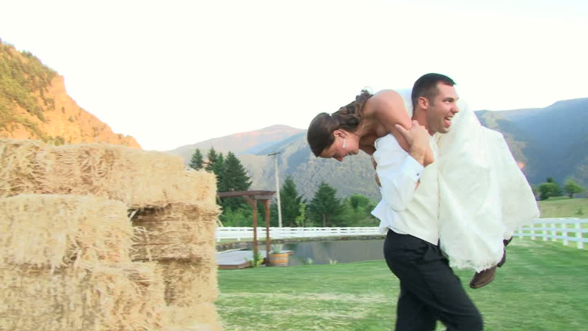 Groom carries his Bride in celebration on their wedding day.