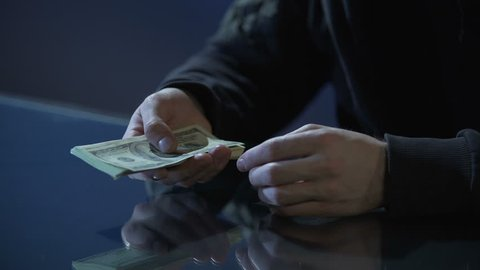 Hands of contract killer or bank robber counting money paid for committing crime