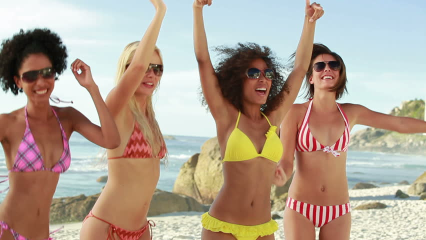 Four women wearing sunglasses partying in their bikinis at the beach