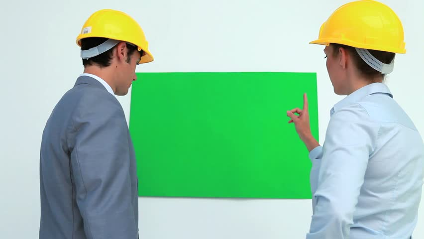 Architects talking in front of a blank space on the wall while wearing safety helmet | Shutterstock HD Video #2341388