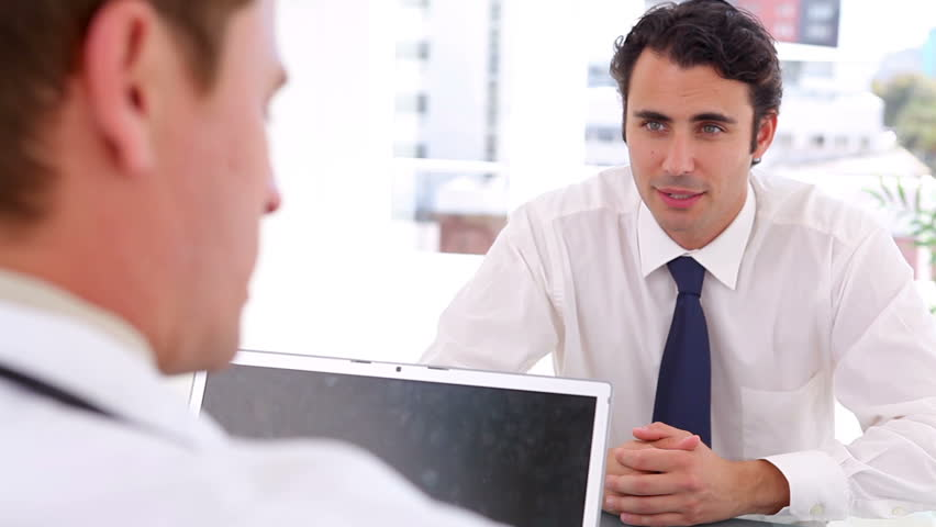 Serious businessman talking to a doctor in a bright office