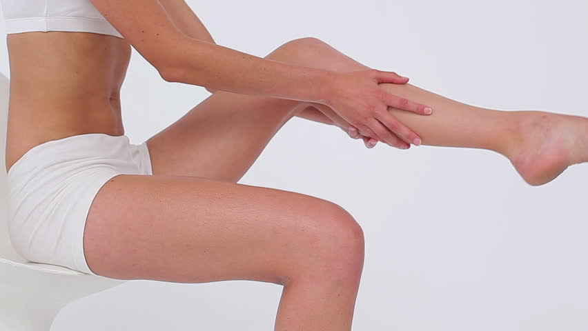 Peaceful woman massaging her thigh against a white background