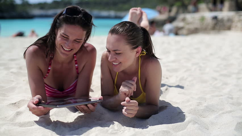 Female friends with tablet computer on the beach, dolly shot