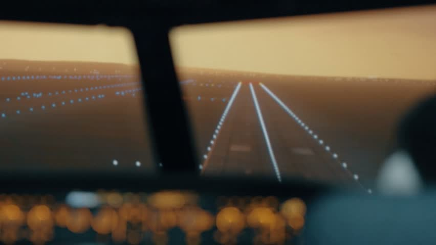 Modern passenger plane descent and landing. Sunset view from the cabin of modern plane to the Airport runway with lighting. Professional male pilots in the cockpit or flight deck control passenger