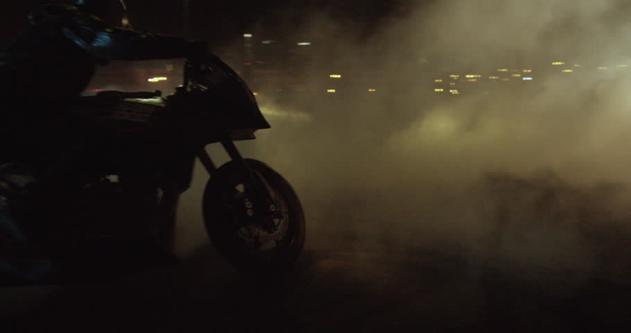 A man on a sport bike does serious burnouts / donuts in slow motion at night then drives off
