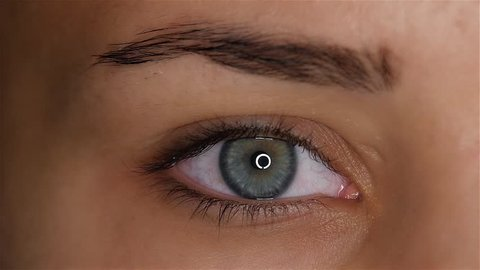 Girl opens her eyes and her pupil increases and narrows. Slow motion. Close up