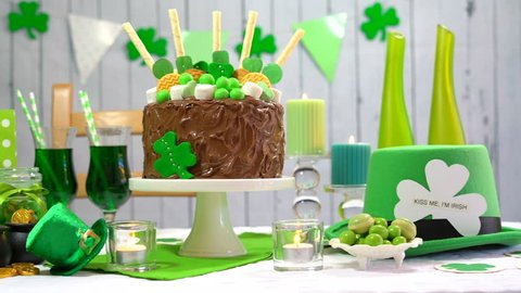 Happy St Patricks Day party table with chocolate cake decorated with cookies and candy, full table.