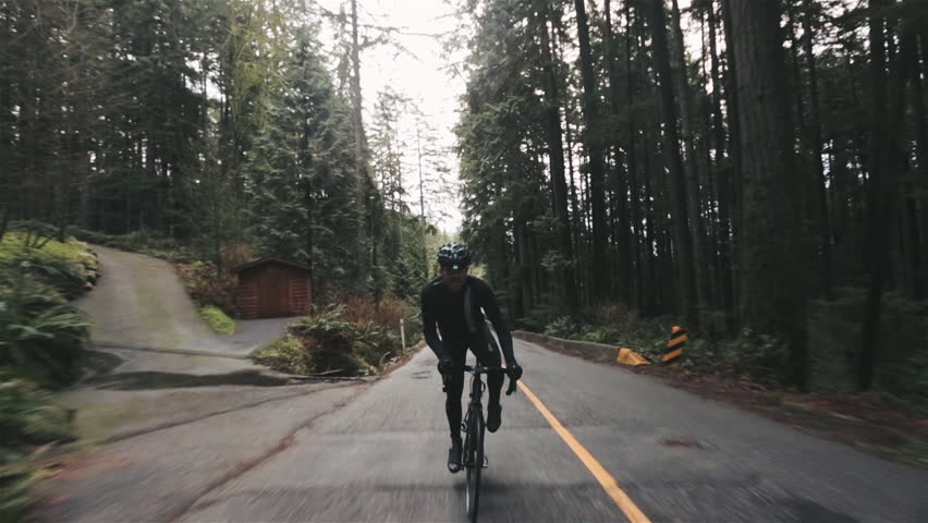 Man Cycling in Vancouver Rainforest Roads