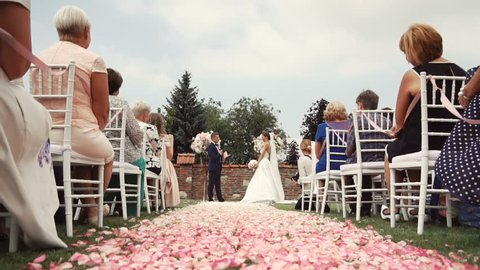 Wedding ceremony location with bride and groom, pink petals path beetwen white guests chairs