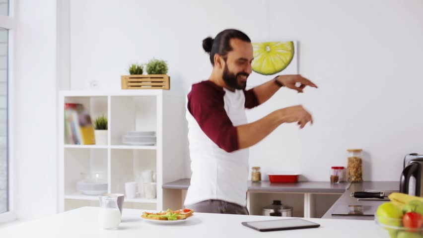 Vegetarian food, healthy eating, people, technology and diet concept - man having sandwiches with coffee for breakfast and dancing to music playing on tablet pc computer at home kitchen | Shutterstock HD Video #23538238