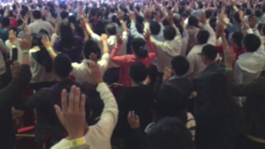 defocused view of people worshiping God with their raised hands