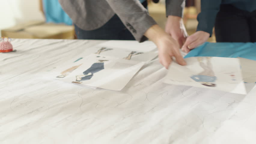 Hands Close-up of a Female and Male Fashion Designer Choosing Sketches for Their New Clothing Collection. Studio is Sunny. Sketches and Fabrics Lay on the Table,  Colorful Fabrics Visible.