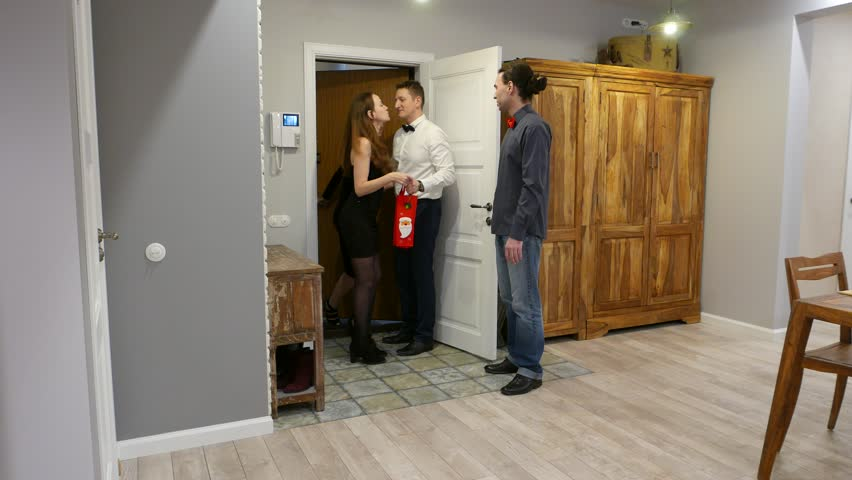 Two guys open door and warmly welcome girlfriends at hallway, young people meet for evening dinner. Women wear black dresses, hearty hugs, light kisses, full length view, modern apartment living room