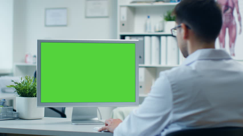 doctoru0027s office male doctor works at his personal computer with green screen assistant modern doctors