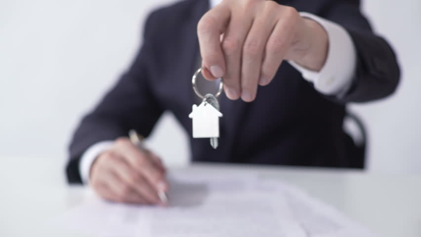 Man holding out key from house or apartment to buyer, signing mortgage agreement | Shutterstock HD Video #23577112