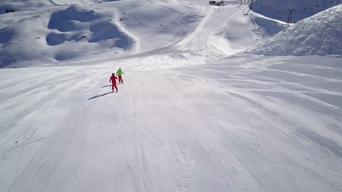 4k aerial footage, drone following two skiers on ski slope in skiing region