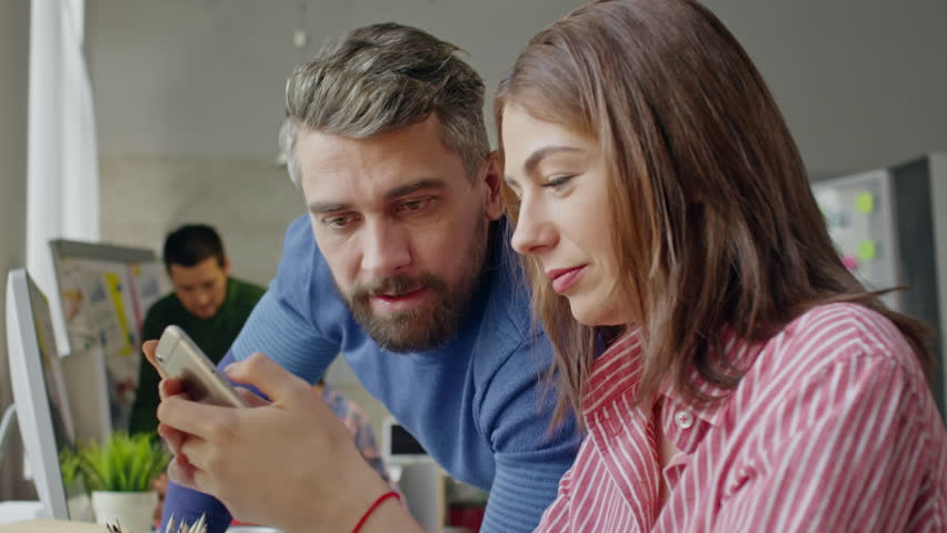 Lockdown on friendly male and female colleagues chatting and browsing internet on mobile phone during break at work | Shutterstock HD Video #23600245