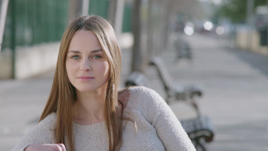 Woman sitting in a bench at the park. She looks at camera concerned, seriously. Close up.   Shutterstock HD Video #23600641