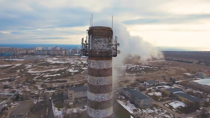 Top of the pipe with steam during the winter heating season (aerial shot). 4K. Pipes of a thermal power plant.