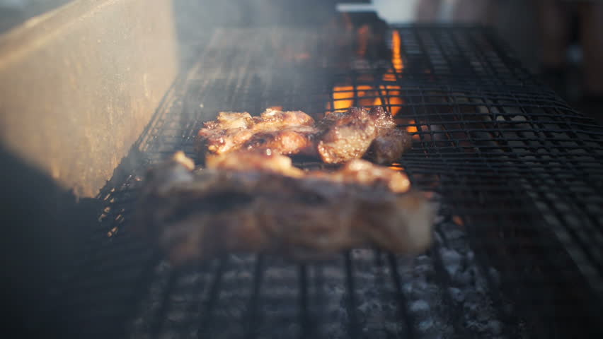 Slow motion shot of meat being turned on a barbecue in summer sun. | Shutterstock HD Video #23642788