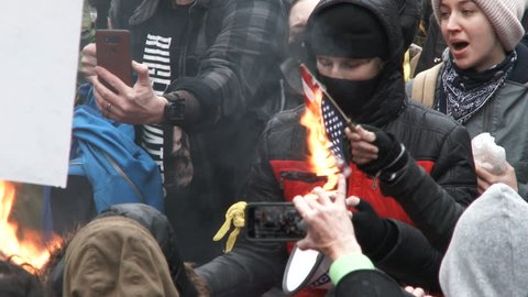PORTLAND, OREGON - CIRCA 2017: Large group of protesters gather and chant Not My President and burn United States of America flags on Donald Trump's inauguration day.