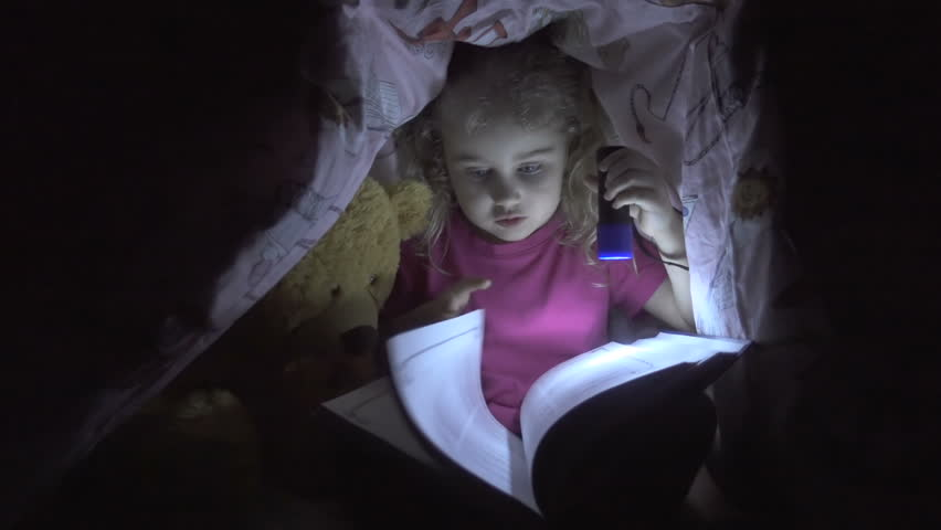 Cute Little Child is Reading a Book With Flashlights at Night. Happy Girl Plays at Home. Funny Lovely Kid Having Fun in Children Room Hiding Under Duvet.