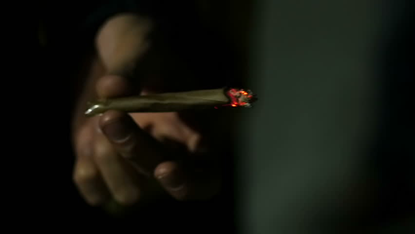 Going in and out of focus: Slow motion close up of male hand holding lit marijuana joint in the dark.