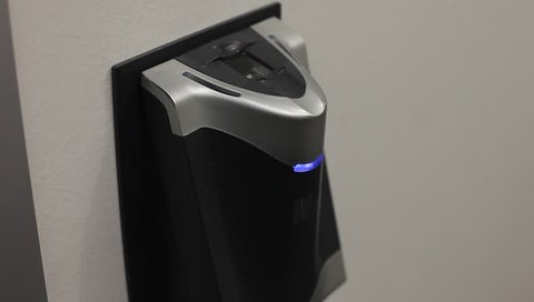 Biometric finger print scanner.  A hand places a badge next to a bio-metric reader and a finger is scanned and authenticated.
