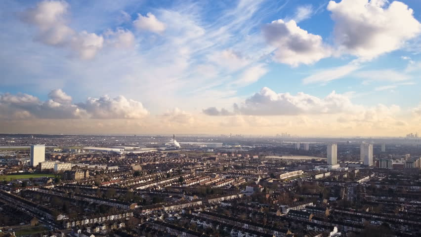 North London suburbs; drone side track. 4K drone video footage looking over the terraced rooftops and high rise flats of the Edmonton Green district of North London on a bright February day.