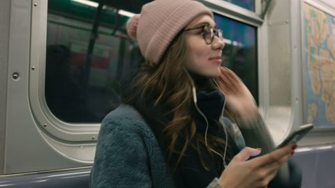 Side view of Young Woman in warm clothes and eyeglasses listening music on smartphone and sitting in metro carriage