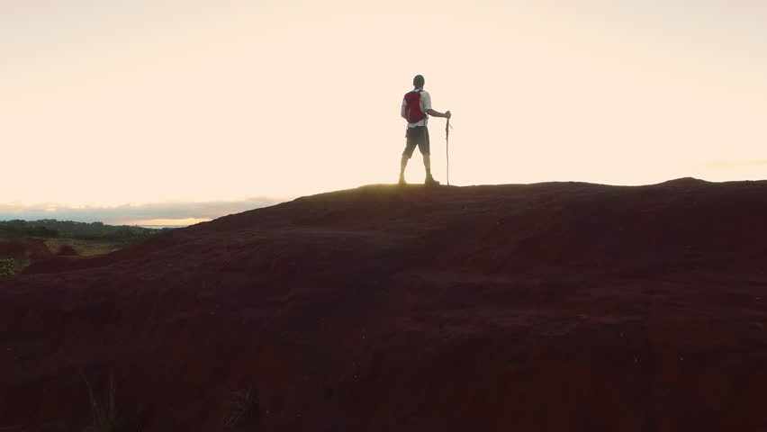 4k drone footage of hiker walking  and looking at view with red backpack in desert mountain terrain at sunset.  | Shutterstock HD Video #23794918