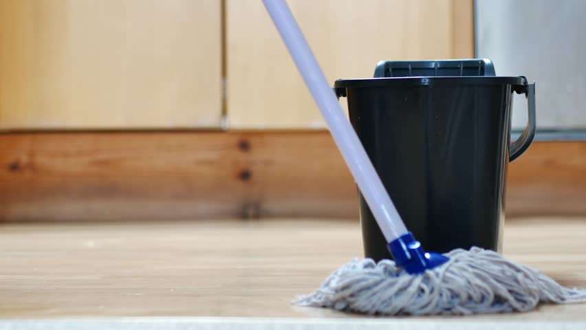 Low Angle Close Up Footage Of Someone Mopping The Kitchen Floor With Mop  And Bucket.