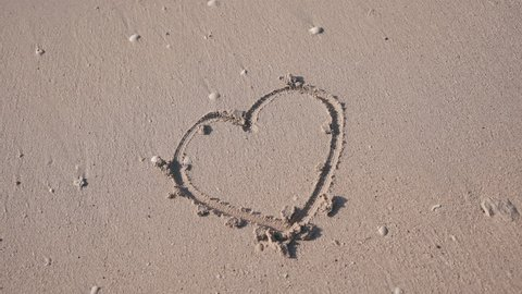 Close-up heart in the sand. Woman's hand draws a heart on the white sand. Love and romance. Beach. Wet sand. Teen girl drawing heart shape on the sand. Handheld shot