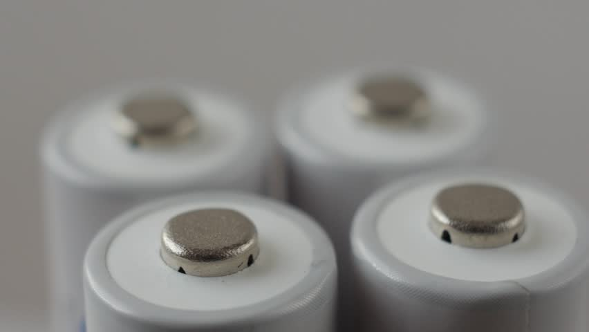 Positive terminals of four batteries slowly rotates on a white background.