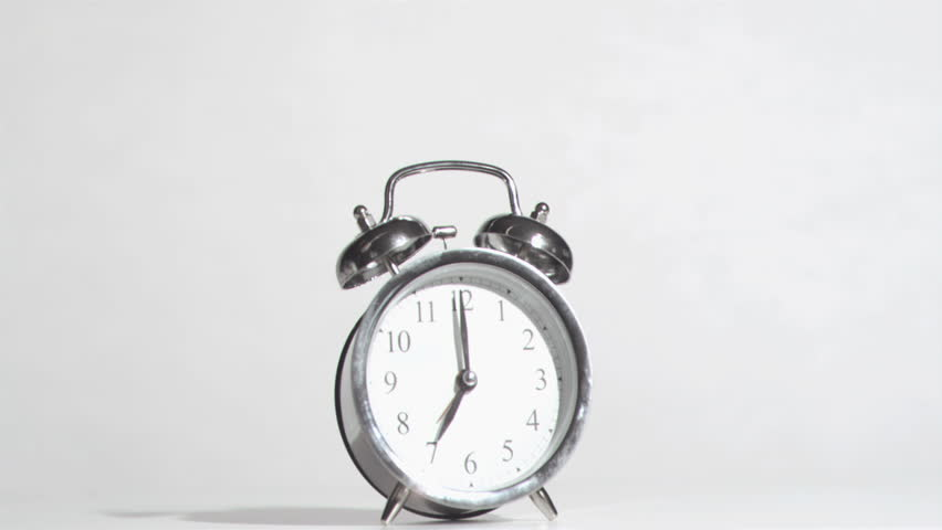 Alarm clock sounds in a super slow motion crushing by a hammer against a white background