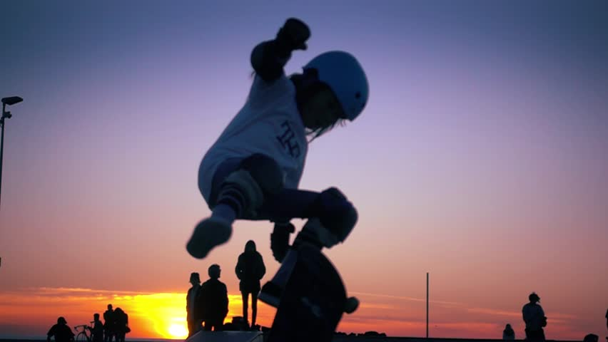Silhouette of skater on skateboard jumping over sunset sky at Venice Beach skate park, California. Slow motion