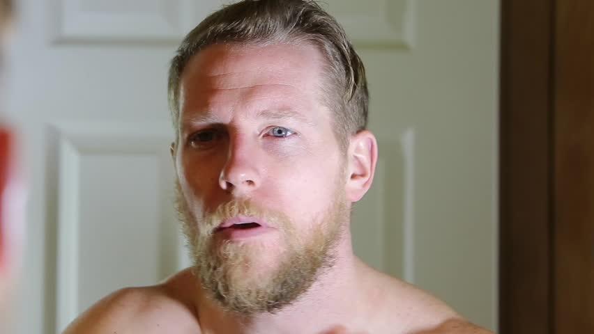 man applies beard oil to his manly facial hair