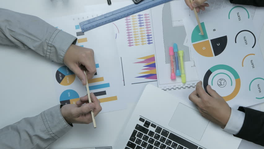 Above view of two businessmen working together at the desk discussing budget, financial charts.   Shutterstock HD Video #23883286