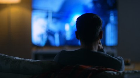 Back View of a Man Sitting on a Couch Watching Movie on His Big Flat Screen TV. Shot on RED EPIC-W 8K Helium Cinema Camera.
