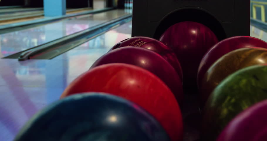 Close-up of balls for bowling play 4k video. Ball returns from ball lift returner. Rolling on alley on background. Bowling game leisure equipment