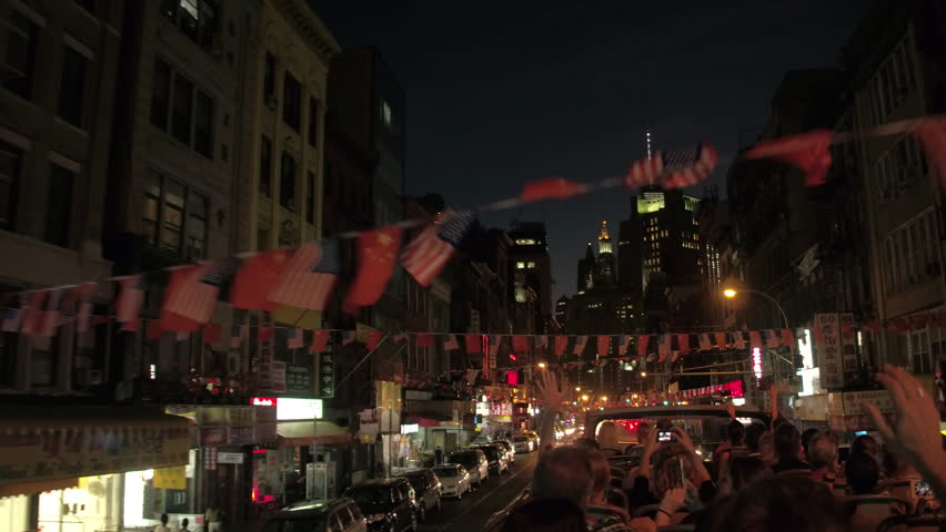 NEW YORK, USA - SEPTEMBER 23rd 2016: Tourists on night excursion driving in doble decker through colorful Chinatown adorned with traditional vibrant flag decorations and illuminated with neon signs | Shutterstock HD Video #23894098