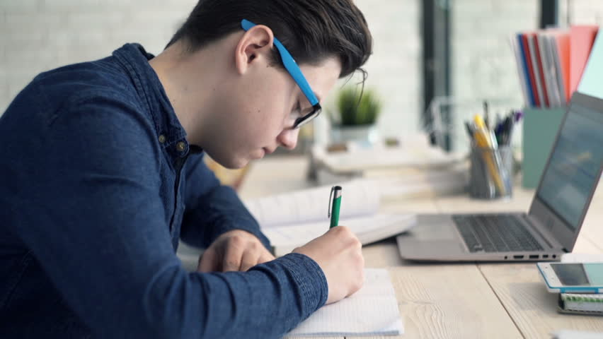 Young teenager doing homework in kitchen at home  | Shutterstock HD Video #23897278
