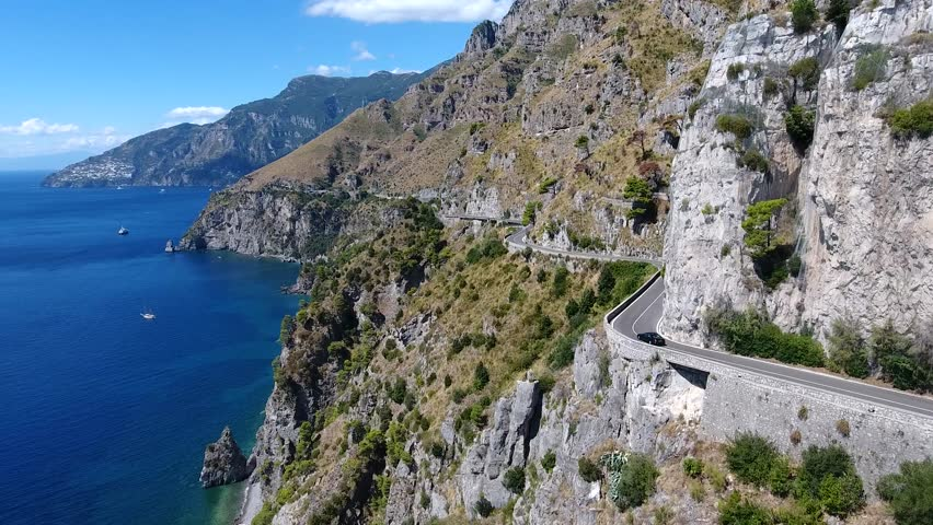Aerial flying past beautiful coastline car driving over cliff road in front of drone amazing Mediterranean landscape and automobile driver maneuvering flexible on curvy ocean road summer vacation 4k