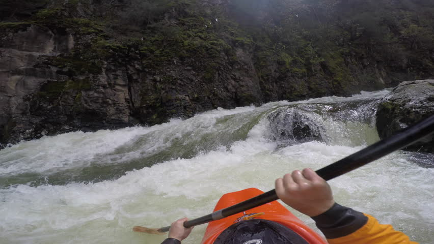 A first person video of a kayaker rolling and flying down a dangerous rapid