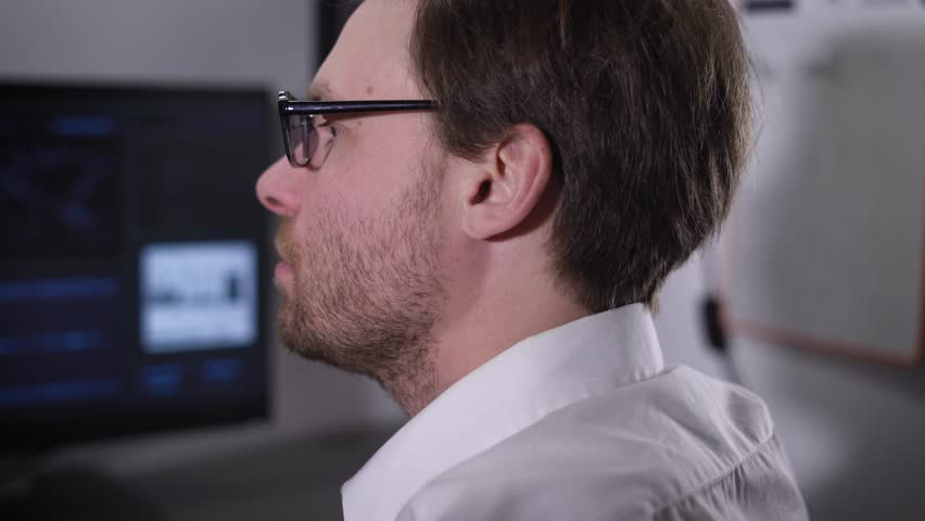 The man with glasses and a white shirt very quickly typing on the computer keyboard and stares at the monitor. Freelancer in the process of working on a new project. | Shutterstock HD Video #23925058