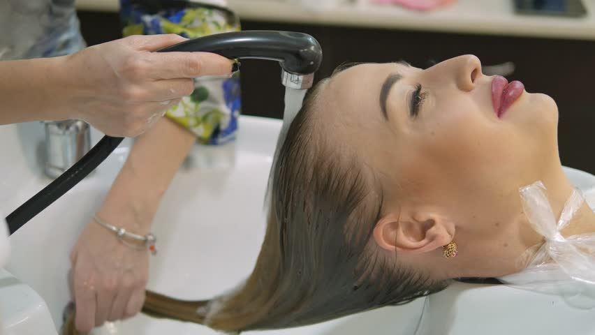Hair Care In The Modern Spa. Woman Having Hair Washed By Hairdresser In Hair  Salon
