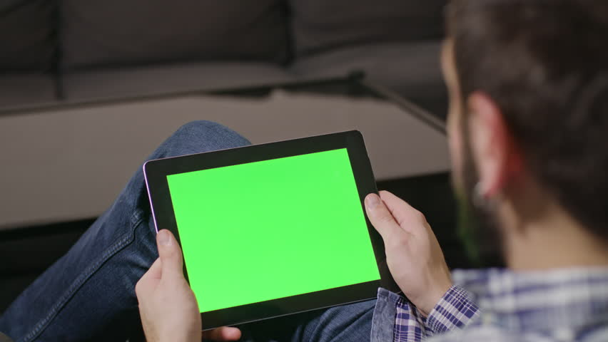 Young man using digital tablet pc with blue screen sitting at home. sliding | Shutterstock HD Video #23961430