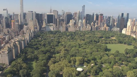 AERIAL ESTABLISHING SHOT: Flying above Central Park along 5th Avenue and towards Downtown Manhattan in sunny New York City. Tall glassy skyscrapers and condominium buildings overlooking Central Park