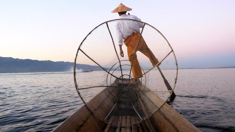Inle Lake fisherman rowing boat in traditional style at sunset, Shan State, Myanmar (Burma).